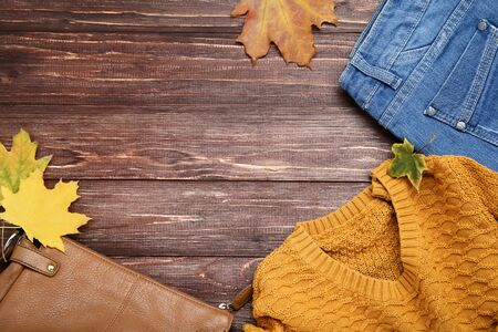 Knitted sweater with jeans, leather bag and maple leafs on brown wooden table