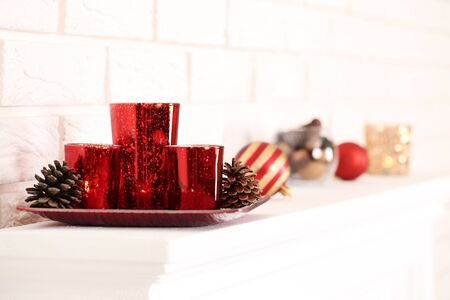 Christmas candles with cones and baubles on white fireplace 写真素材