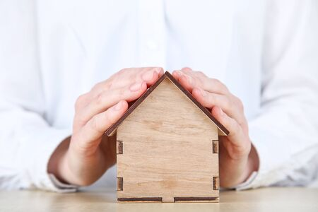 Female hands holding wooden house model Stok Fotoğraf
