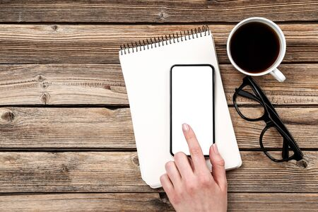 Smartphone in hand with cup of coffee and notepad on wooden background Foto de archivo