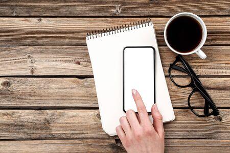 Smartphone in mano con tazza di caffè e blocco note su sfondo di legno Archivio Fotografico