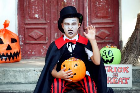 Young boy in halloween costume holding pumpkin bucket with candies and showing teeth