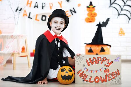 Young boy in costume with pumpkin and text Happy Halloween