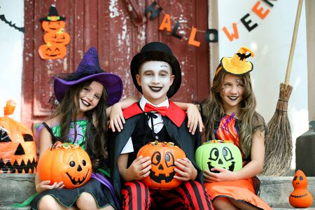 Two young girls and boy in halloween costumes sitting on porch and holding pumpkin buckets full of candies
