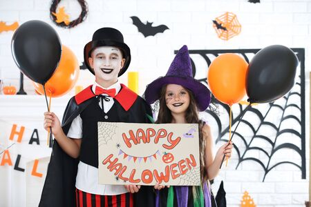 Young girl and boy in costumes with ballons and holding paper with text Happy Halloween