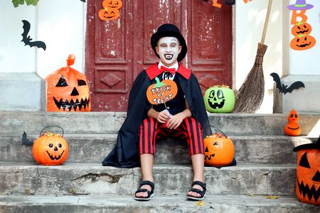 Young boy in halloween costume sitting on porch and holding paper pumpkin with text Trick or Treat