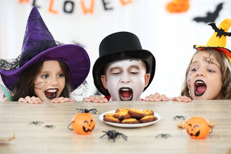 Young two girls and boy in halloween costumes looking on the cookies Stock fotó