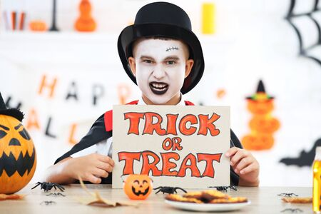 Young boy in halloween costume holding paper with text Trick or Treat Stock fotó