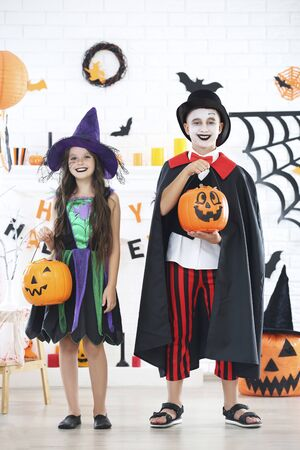 Young girl and boy in halloween costumes with pumpkin buckets