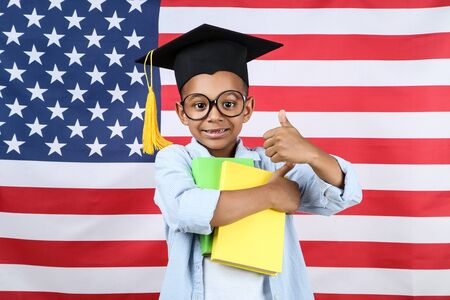 Cute boy in graduation cap with books on american flag background 스톡 콘텐츠
