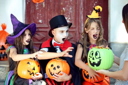 Two young girls and boy in halloween costumes sitting on porch with pumpkin buckets full of candies