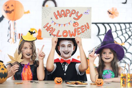 Beautiful two girls and boy in costumes sitting by the table and holding paper with text Happy Halloween