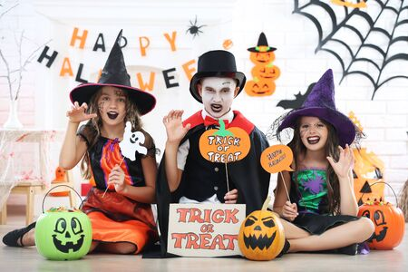 Young two girls and boy in halloween costumes holding paper ghost, pumpkins and candies in buckets Stock fotó