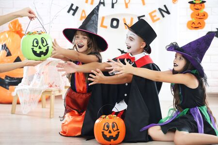 Young two girls and boy in halloween costumes with candies in pumpkin buckets Stock fotó