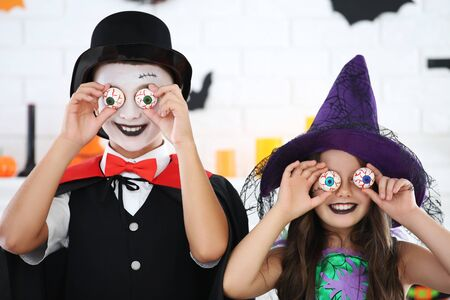 Young girl and boy in halloween costumes holding scary eyes