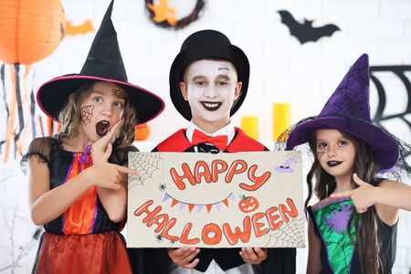 Young two girls and boy in costumes holding paper with text Happy Halloween