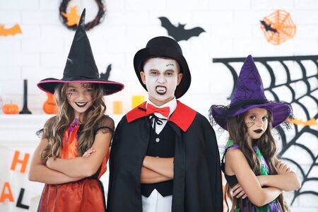 Young two girls and boy in halloween costumes