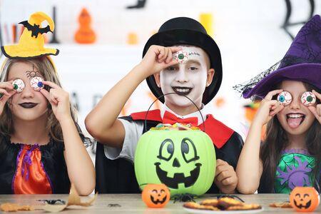 Hermosas dos niñas y un niño en disfraces de halloween sentados junto a la mesa con ojos blancos y caramelos en un cubo de calabaza Foto de archivo