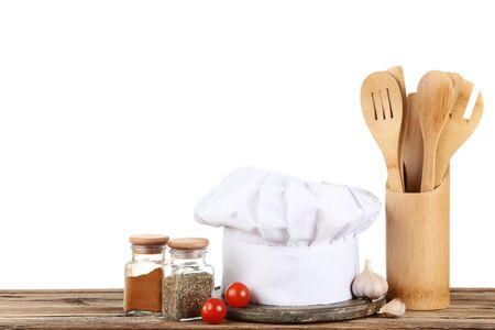 Kochmütze mit Gewürzen in Gläsern und Gemüse auf braunem Holztisch