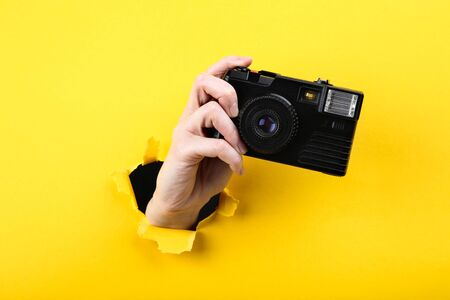 Hand holding camera from yellow torn paper