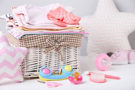 Clothes in basket with toy and baby supplies on white background Standard-Bild - 129975876
