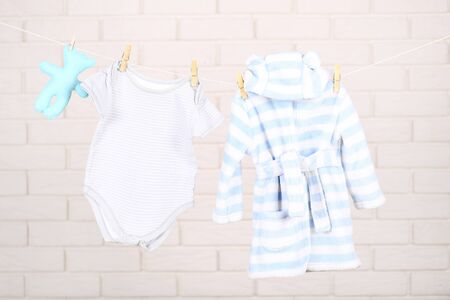 Baby clothes with soft toy hanging on brick wall background