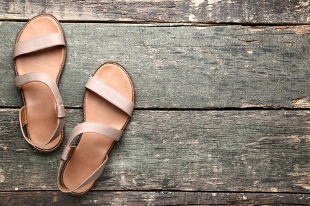 Female beige sandals on grey wooden table