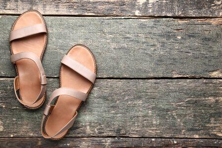 Vrouwelijke beige sandalen op grijze houten tafel