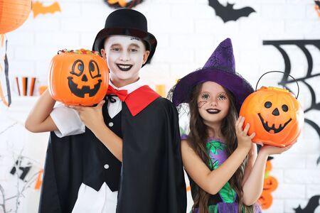 Niña y niño en disfraces de halloween con cubos de calabaza Foto de archivo