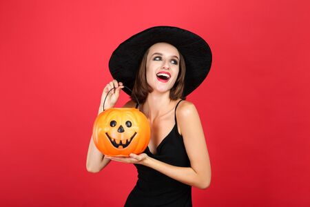 Happy young woman in black halloween costume holding pumpkin bucket on red background Archivio Fotografico