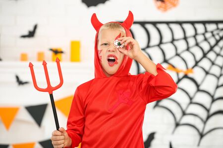 Young boy in halloween costume holding white eye