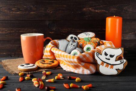 Halloween-Lebkuchenplätzchen mit Bonbons auf Holztisch