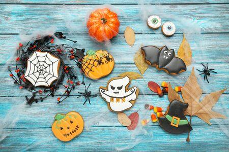 Biscotti di panpepato di Halloween con foglie di acero secche su tavola di legno blu Archivio Fotografico