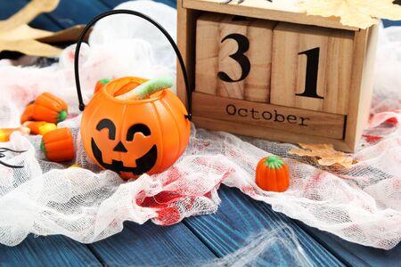 Halloween candies with wooden calendar and pumpkin bucket with candies