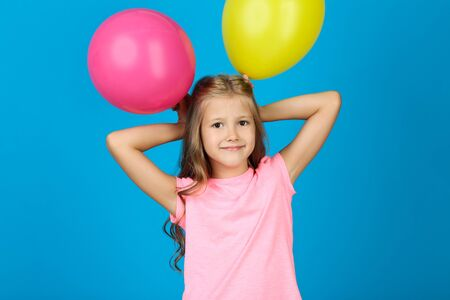 Pretty little girl with rubber balloons on blue background