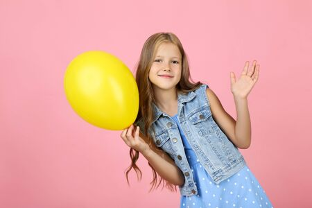 Pretty little girl with yellow rubber balloon on pink background