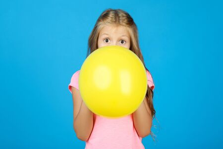 Pretty little girl blowing yellow balloon on blue background
