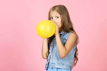 Pretty little girl blowing yellow balloon on pink background
