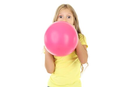 Pretty little girl blowing pink balloon on white background