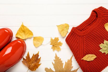 Woolen sweater with red rubber boots and autumn leafs on white wooden table Stok Fotoğraf