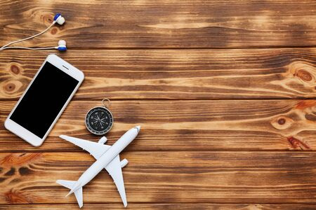 Airplane model with smartphone, compass and earphones on brown wooden table Stockfoto