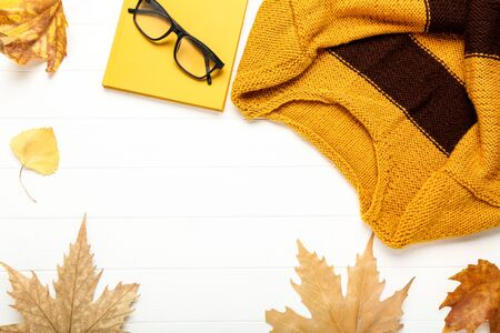 Woolen sweater with autumn leafs and eyeglasses on white wooden table