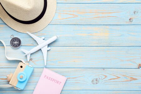 Airplane model with passport, compass, hat and camera toy on blue wooden table