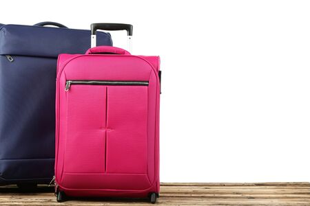 Blue and pink suitcases on wooden table
