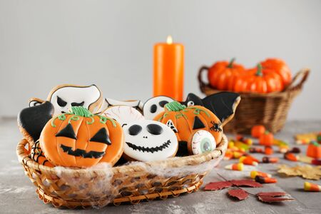 Halloween gingerbread cookies in basket with candies on grey background Foto de archivo