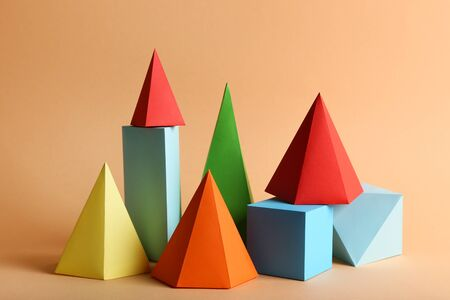 Colorful paper geometric figures on beige background
