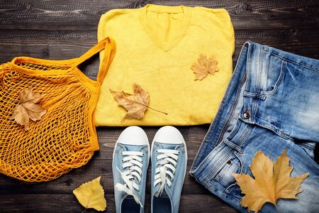 Fashion clothing with autumn leafs on brown wooden table