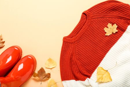 Woolen sweater with autumn leafs and red rubber boots on beige background