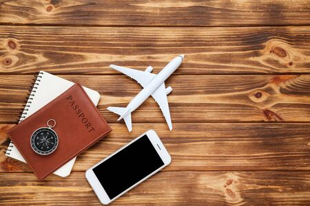 Airplane model with passport, smartphone and compass on brown wooden table