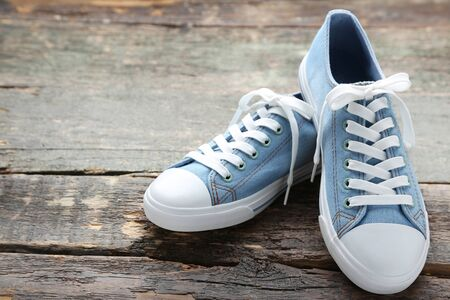 Pair of blue sneakers on grey wooden table
